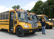 Transportation Supervisor Larry Holland is pictured with three new 78-passenger school buses, No. 13-08, No. 13-34 and No. 13-44.