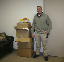 LPD Detective Jason Roberts is pictured with boxes of merchandise involved in a scam. (Photo by D. Gregory)