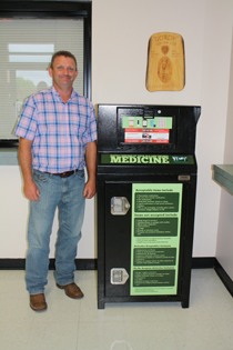 Pictured above, Macon County Sheriff Mark Gammons displays the medication disposal bin located in the lobby of the sheriff's office. (Photo by: J. Willliams)